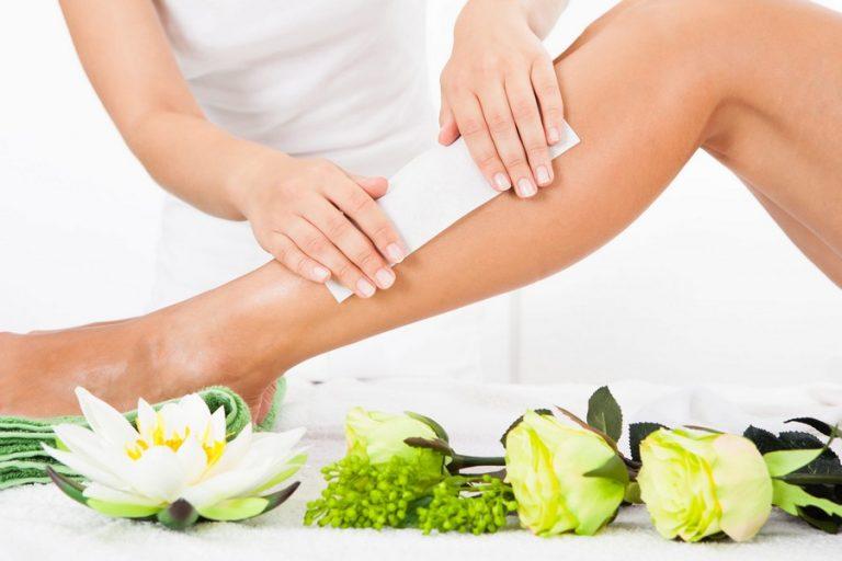 Beautician Waxing A Woman's Leg In Spa